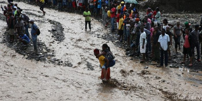 epa05572081 A group of people try to cross the river La Digue, after the colapse of the only bridge that connects to the south after the passing of hurricane Matthew in the country, in Petit Goave, Haiti, 05 October 2016. The hurricane Matthew left at least nine dead on last 04 October. The impact of Hurricane Matthew in Haiti, which left at least nine dead and thousands displaced, mainly in southwestern communities, forced the electoral authorities to postpone Sunday's election.  EPA/Orlando Barria